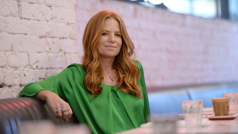 Patsy Palmer in green top sitting in london cafe
