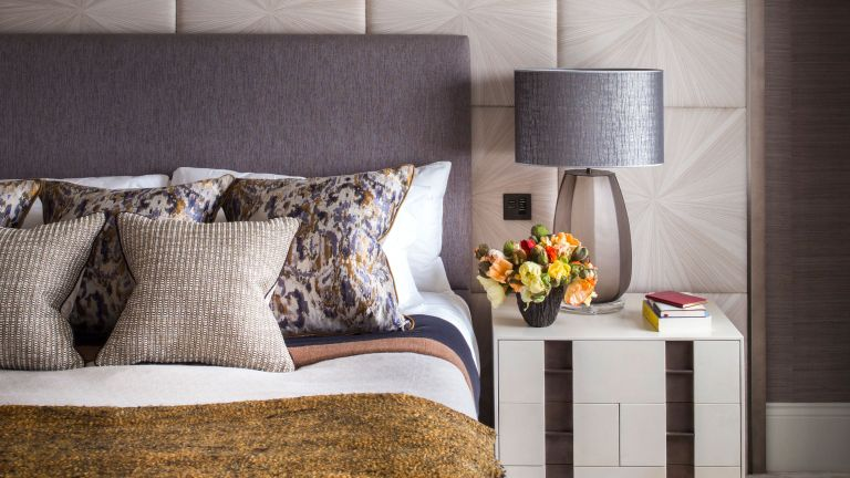 An example of guest bedroom ideas showing a bed with a gray headboard, cushions and a gray bedside lamp