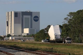 The Orion spacecraft, secured atop a transporter in its shipping container, is carried to the Neil Armstrong Operations and Checkout Building at NASA's Kennedy Space Center in Florida on March 25, 2020. The spacecraft was transported to Kennedy in NASA's Super Guppy aircraft from the agency's Plum Brook Station in Ohio.
