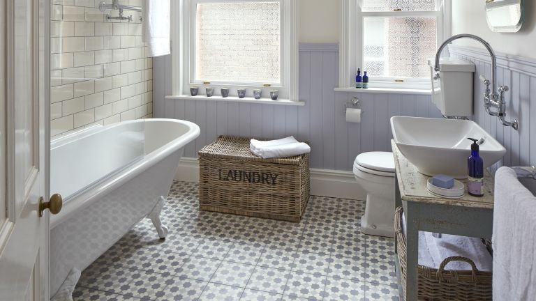 An example of bathroom floor tile ideas showing grey and white mosaic floor tiles in a bathroom with a white free standing bath and a laundry basket