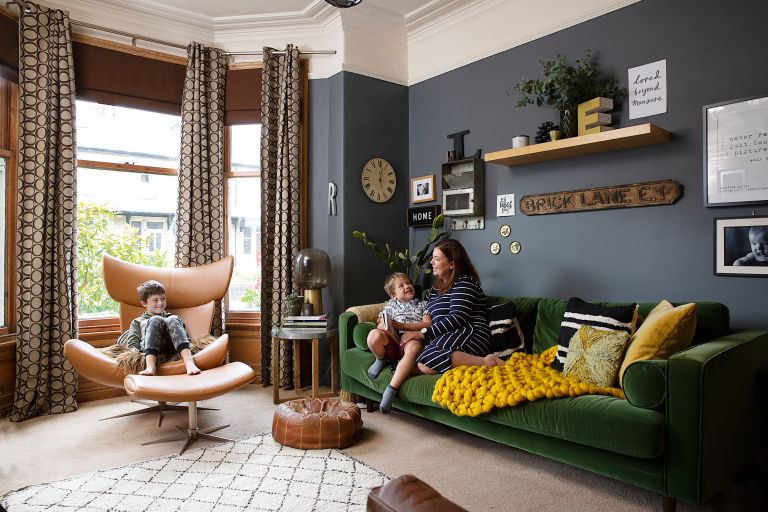 A wide shot of the dark navy living room with green velvet sofa, shelving, framed art prints and a brown leather butterfly chair in the bay window