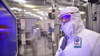 Intel manufacturing shot of employee in bunny suit (protective gear) in front of screen