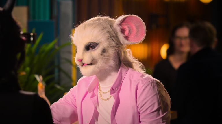 A film still from Sexy Beasts Netflix dating show which depicts the 'mouse' in a bright pink jacket sitting at a bar