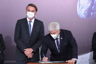 Marcos Pontes, Brazil's Minister of Science, Technology and Innovation signs the Artemis Accords next to Brazil's President Jair Bolsonaro on June 15, 2021.