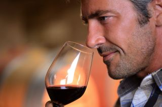 A man smells a glass of wine before tasting it.