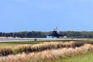 Space shuttle Discovery touches down on Runway 15 at the Shuttle Landing Facility at NASA's Kennedy Space Center in Florida. Landing was at 11:57 a.m. EST