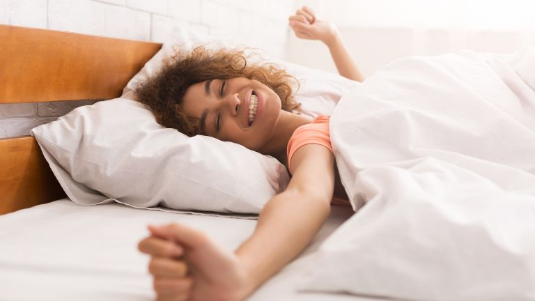Woman stretching and smiling in bed