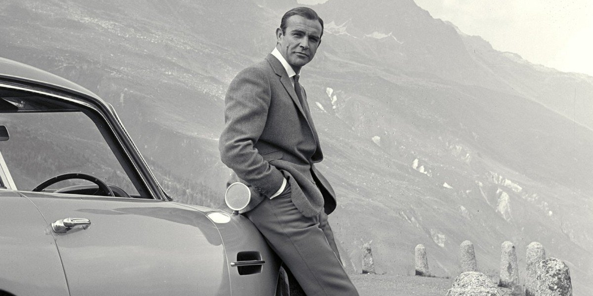 Goldfinger Sean Connery leaning against his Aston Martin
