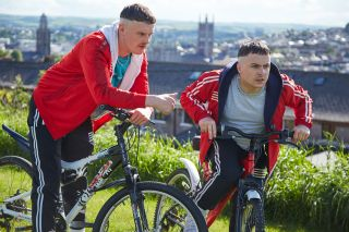 Jock and Conor on their bikes with Cork City in the background