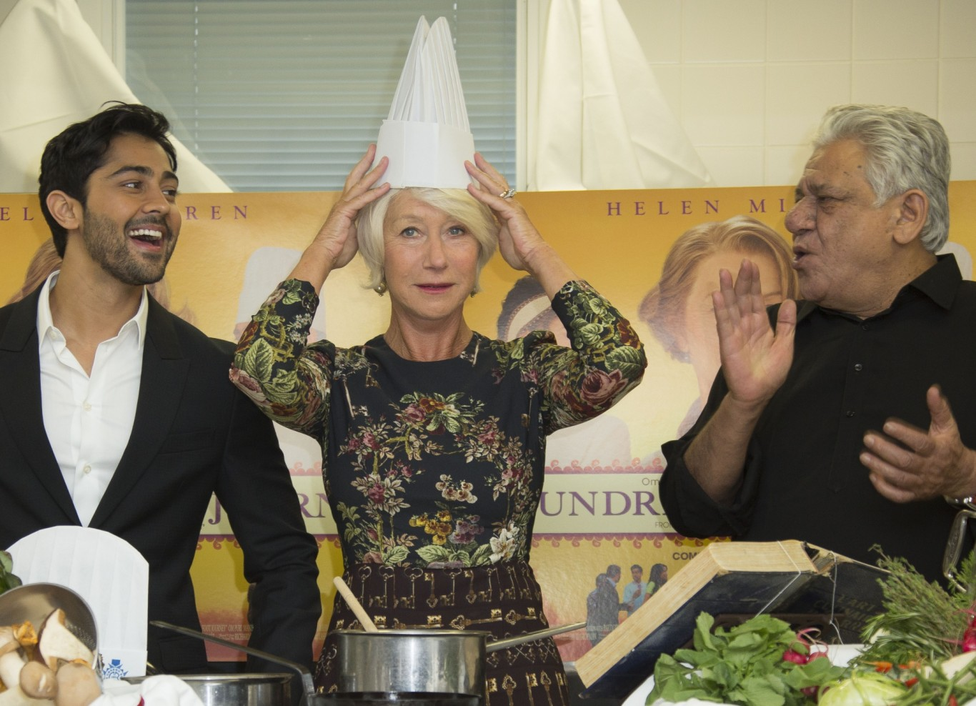 Helen Mirren puts on a chef's hat as actors Om Puri, right and Manish Dayal look on, at culinary school le Cordon Bleu for food-themed photo call for the film The One Hundred Foot Journey