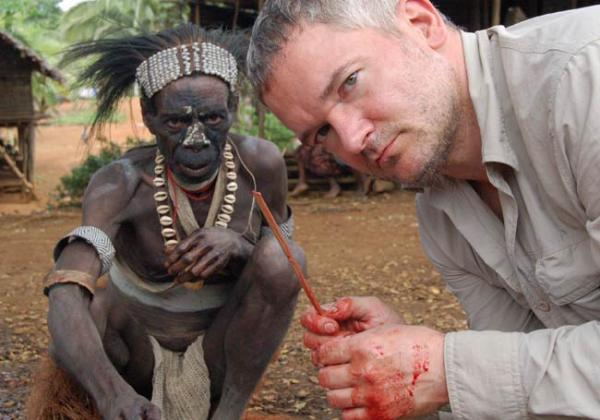 Papua New Guinea, Western Province: Piers Gibbon with song leader Tidikawa, who was responsible for identifying 'magic men' who would be killed and eaten. Gibbon is helping butcher a pig with the bamboo knife he holds. The same sort of knife was once used to butcher humans.