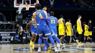 Tyger Campbell #10 of the UCLA Bruins celebrates with Jaime Jaquez Jr. #4 after defeating the Michigan Wolverines 51-49 in the Elite Eight round game of the 2021 NCAA Men's Basketball Tournament at Lucas Oil Stadium on March 30, 2021 in Indianapolis, Indiana.