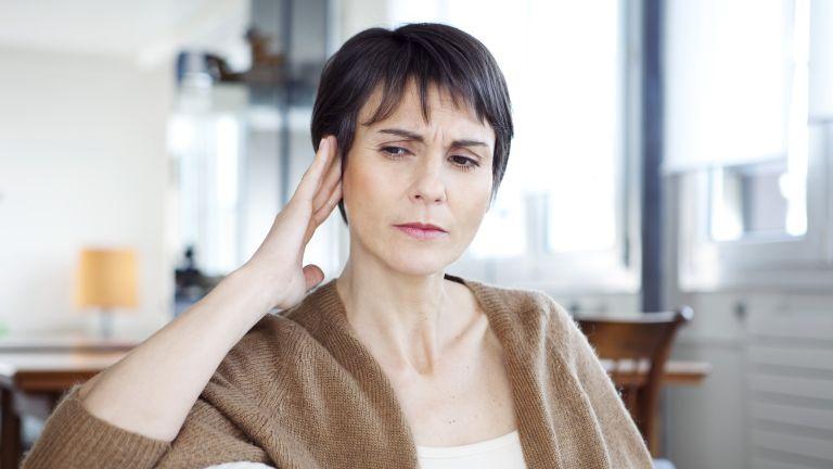 Woman experiencing tinnitus