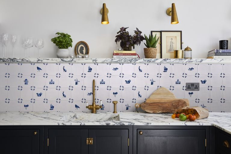 How to install a backsplash, shown in a white kitchen with Delft tiles, a white marble countertop and shelf, black cabinetry and antique-style gold faucet and wall lighting.
