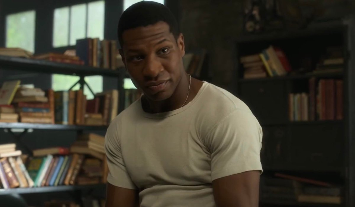 Jonathan Majors sits in front of shelves stocked with books in Lovecraft Country.
