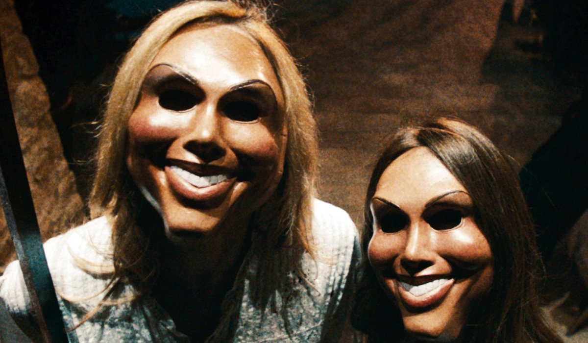 Two Purgers wearing creepy masks in The Purge.