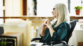 Best ergonomic office chairs: An older woman with grey-blonde hair relaxes in a supportive home office chair