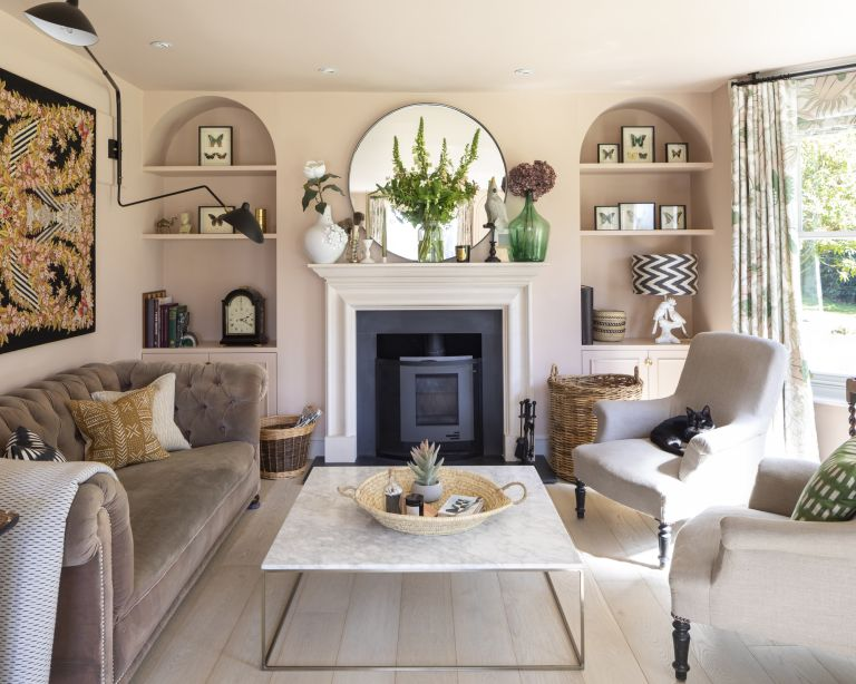 A neutral living room with marble fireplace, brown velvet sofa and two taupe armchairs