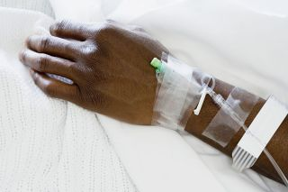 Close up of patient's arm with IV in hospital bed.