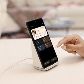Imagen del teléfono Pixel 6 sobre el Pixel Stand, con el usuario interactuando con la pantalla circundante, incluidas las opciones de carga y el rendimiento en modo silencioso.