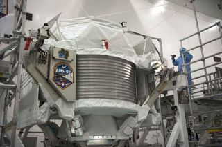 Technicians examine the $2 billion Alpha Magnetic Spectrometer instrument in a work stand ahead of its planned launch on NASA's space shuttle Endeavour. The AMS instrument will search for cosmic rays from the International Space Station.