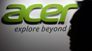 A shadowy man walks by the green Acer logo