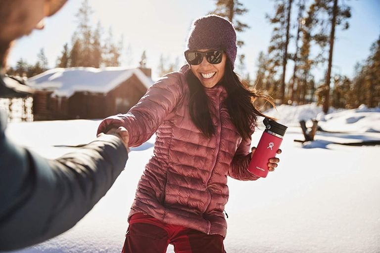 woman in snow holding hydro flask one of the best coffee mugs for travel