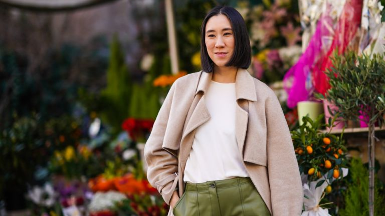 Eva Chen with a paper cut bob wearing a beige long coat, a white t-shirt, green leather pants, pointy shoes, outside Koche x Pucci, during Milan Fashion Week Fall/Winter 2020-2021 on February 20, 2020 in Milan, Italy.