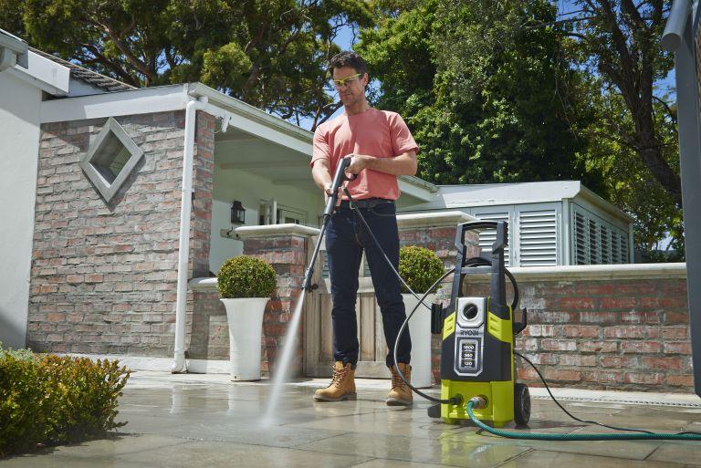 man cleaning a drive with Ryobi RPW120B High Pressure Cleaner