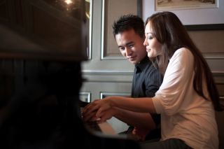 couple plays piano together