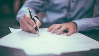 Photo of a man signing a contract. Image: Helloquence on Unsplash