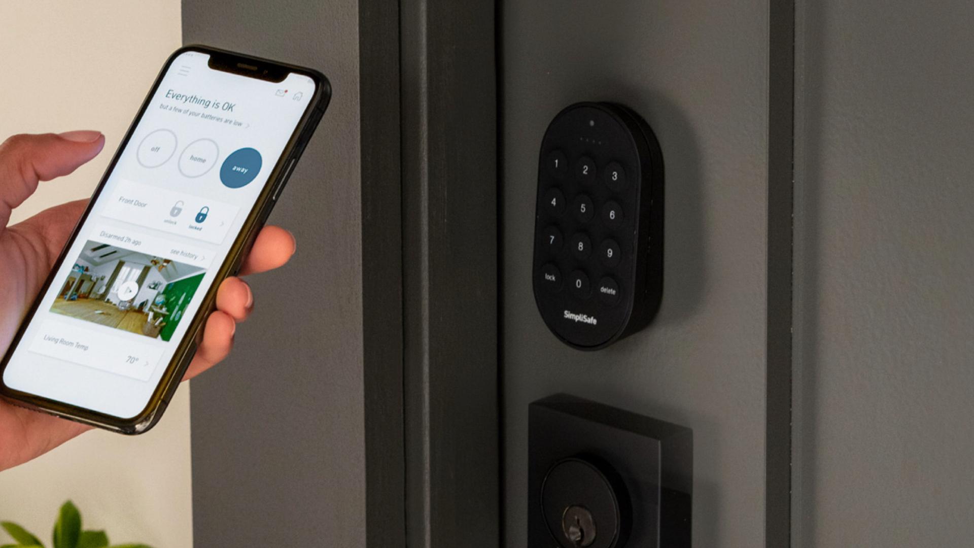 Man holds up SimpliSafe app to the SimpliSafe door lock