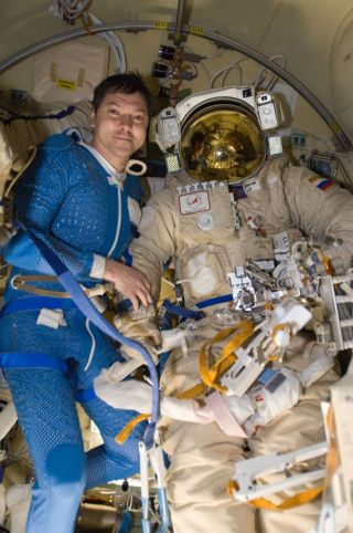 Russian cosmonaut Oleg Kononenko, Expedition 30 flight engineer, poses for a photo with a Russian Orlan spacesuit after a spacewalk outside the International Space Station on Feb. 16, 2012.