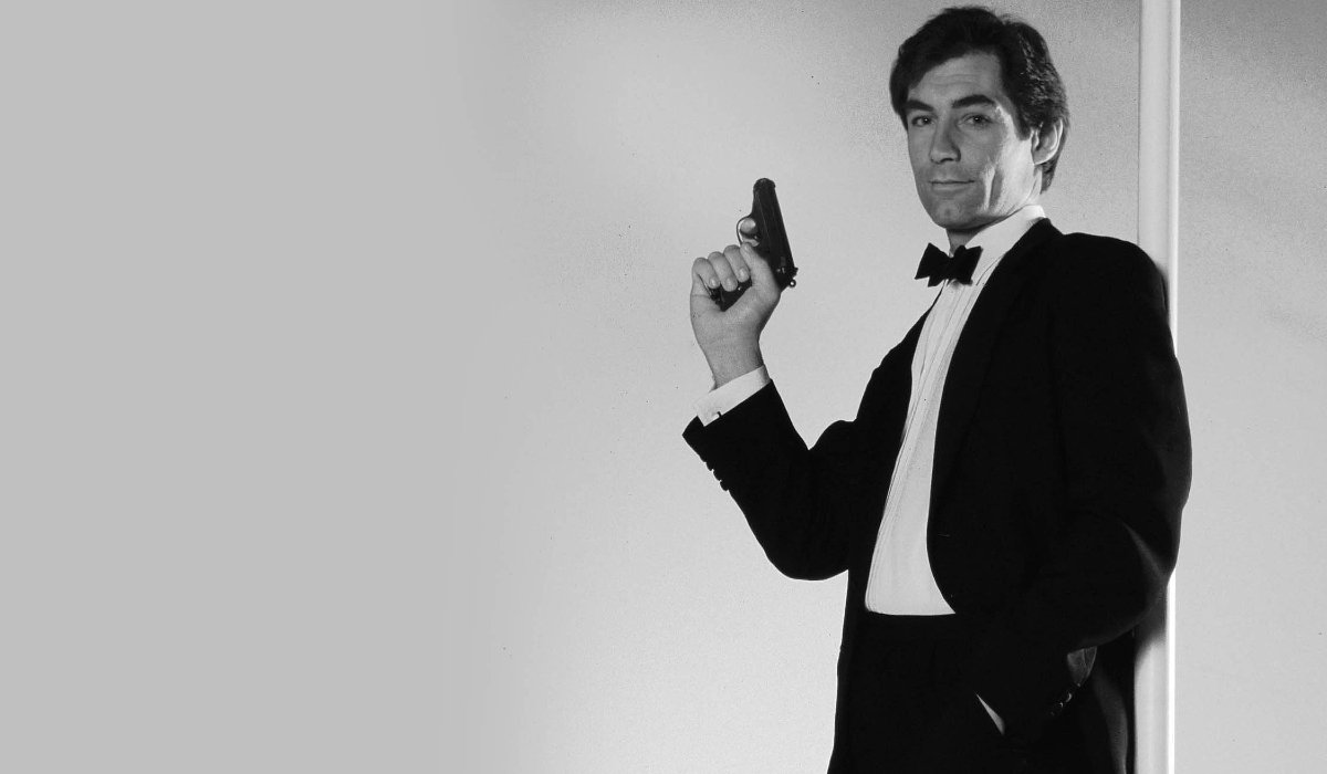 The Living Daylights Timothy Dalton poses with his gun, standing against a pole
