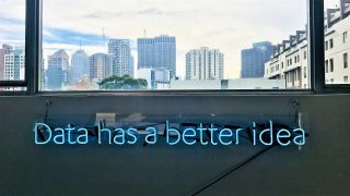 Office wall with neon 'Data has a better idea' sign