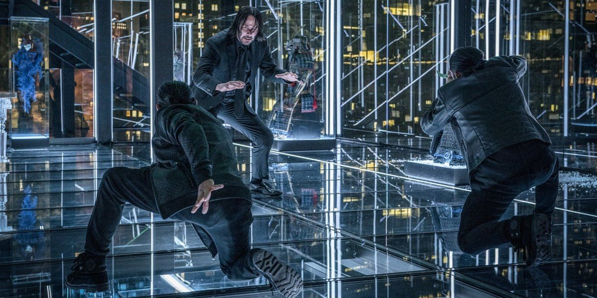 John Wick (Keanu Reeves) trying to not get thrown through glass in John Wick: Chapter 3 -- Parabellum