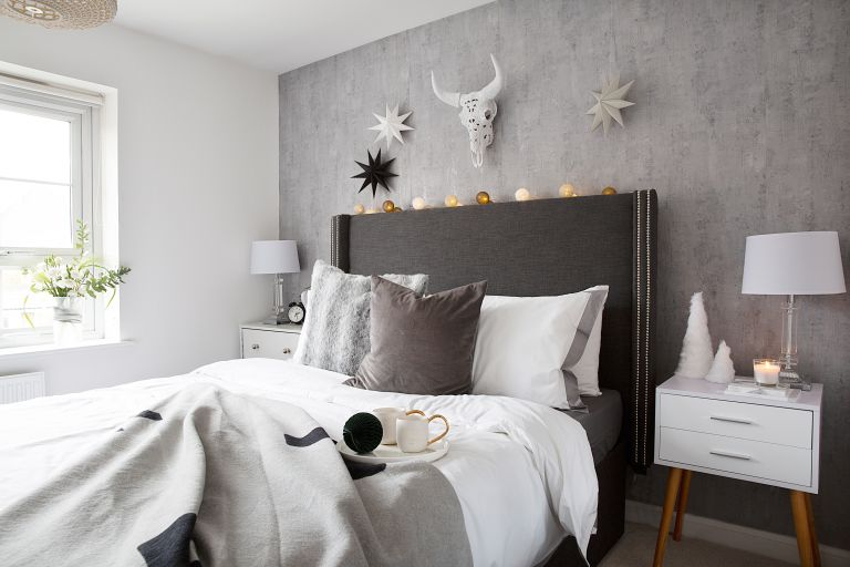 Bed with grey oversized headboard against concrete-effect wallpaper with white and oak modern bedside tables
