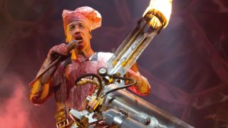 A picture of Till Lindemann on stage with a flame thrower