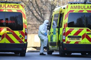 A member of the ambulance service wearing personal protective equipment is seen leading a patient (unseen) into an ambulance at St Thomas' Hospital in London on March 24, 2020.