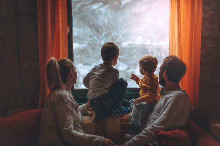 family looking out of a window in the cold