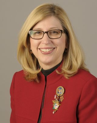 Researcher Teresa Woodruff is posed before a grey wall, wearing a red coat. She has blond hair and large glasses.