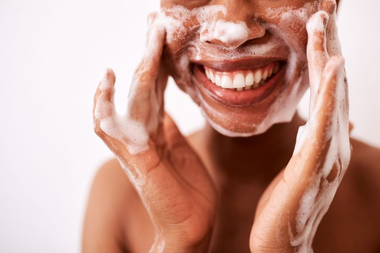 Studio shot of a woman washing her face against a white background