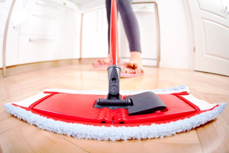 Cleaning a wooden floor with a dry mop