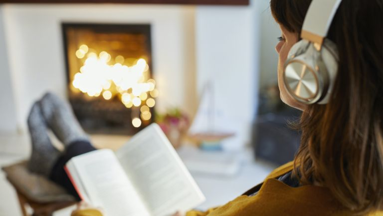 Woman with headphones reading in living room - stock photo