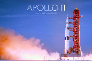 "A poster for ""Apollo 11"" shows the mission's Saturn V rocket on the launch pad."