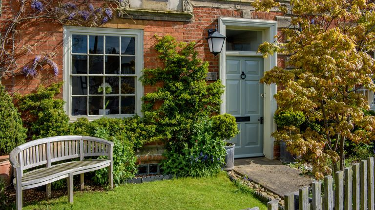A front garden with grass, a bench and wisteria climbing the house exterior