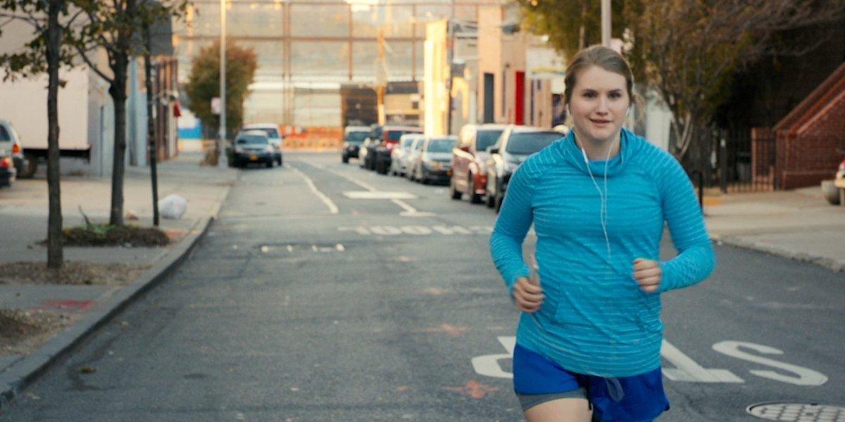 Brittany Runs A Marathon Jillian Bell running down the street, with headphones on