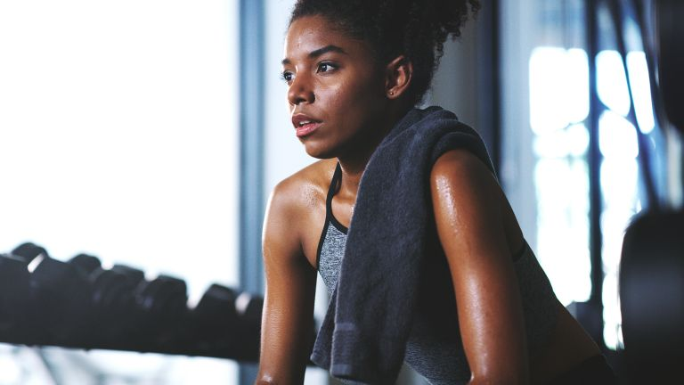 Woman with a towel over her shoulder looking sweaty after finishing a workout