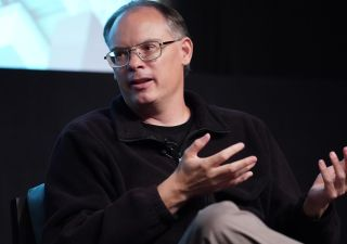 Tim Sweeney sits on a stage, gesturing with his hands.