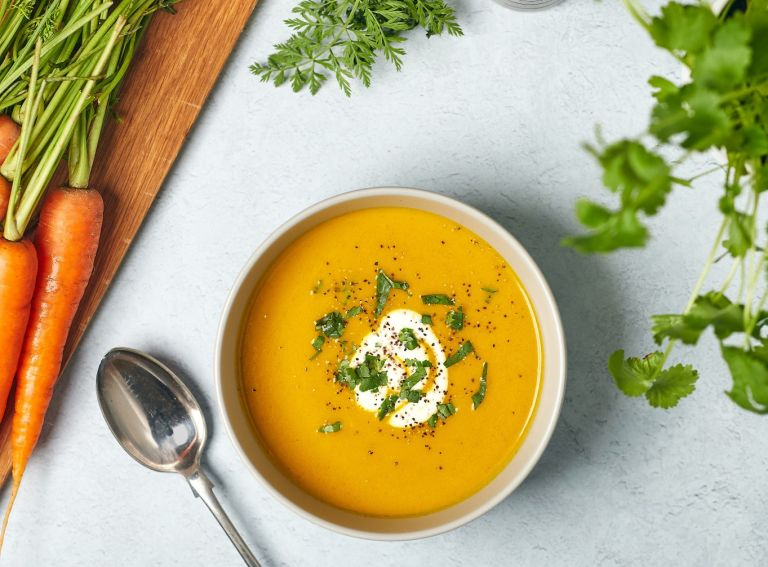 A warm bowl of roasted carrot and coriander soup surrounded with fresh ingredients